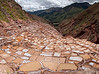 These salt ponds have been in use since pre-Inca times.  A small, salty, warm water spring exits the mountains behind and is channeled into these pools by opening and closing rock gates that control water flow along the perimeter channels