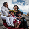 Girls & kids posing on the faux stone work over the central fountain on the main square - Plaza de Armas - Cusco - Peru