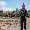Cuyuni kid flying a selfmade kite - Cuyuni - Quispicanchi - Cusco - Peru