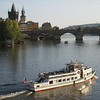 Prague - the Charles Bridge and boat traffic in the late afternoon.