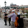 """Prague - Musicians on the Charles Bridge.  There always seem to be a variety of street musicians performing on the bridge, and some of them are really good!  This group was playing a type of Dixieland Jazz.  The percussionist was using a Washboard with a couple of kitchen """"whisks"""".  Prague Castle and St. Vitus Cathedral can be seen in the background."""