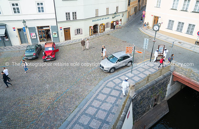 Looking down on cobbled street with passing tourists, shops and boat trip vendors