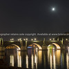 Moon in dark night sky above Illuminated bridge arches and reflections across Vltava River with reflections in calm water