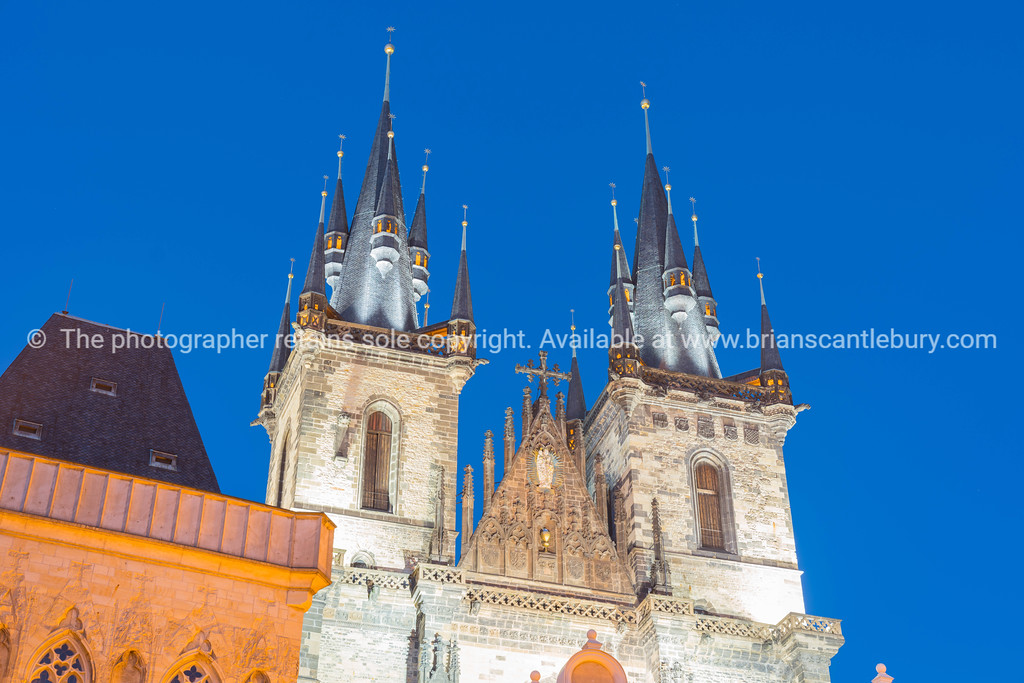 Illuminated buildings and gothic towers of Church of Our Lady of Tyn against dark sky.