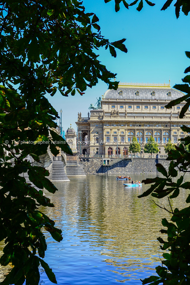 Vltava River view across to National Theater framed by dark trees and leaves