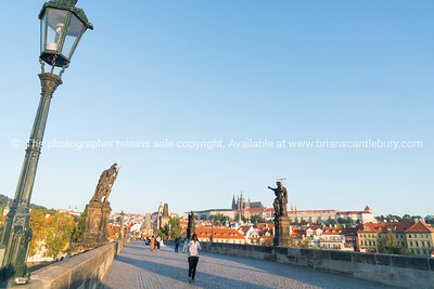 Charles Bridge before sunrise tourists walking across under staute of St John Baptist pointing way.