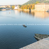 Buildings on side of Vltava River caught in sunrise while man fishes from boat from Charles Bridge