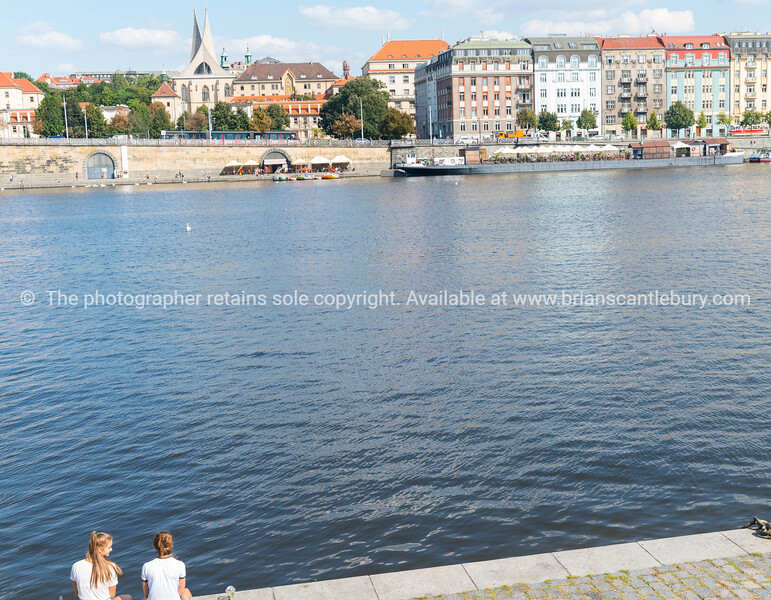 Characteristic architecture and tourist boats alongside promenade across river