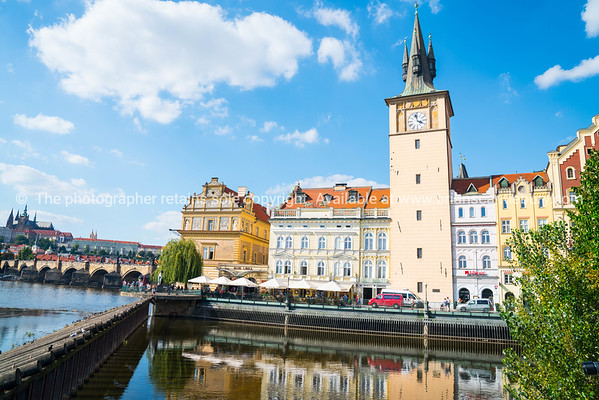 Clock Tower rises over  street alongside Vltava River near Charles Bridge