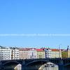 Colorful architecture across Vltava River and bridge under clear blue sky.