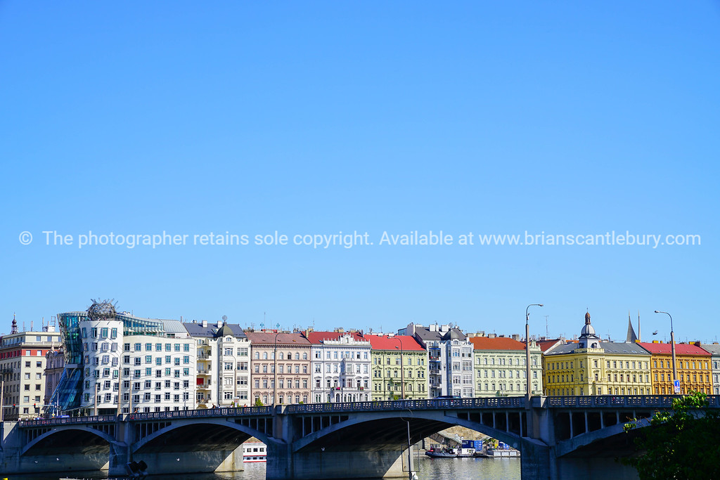 Colorful architecture across Vltava River and bridge under clear blue sky.