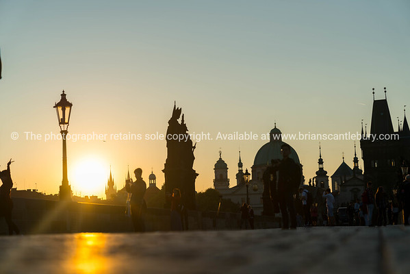 Low point of view image of unrecognizable silhouettes of  people on Charles Bridge at sunrise.