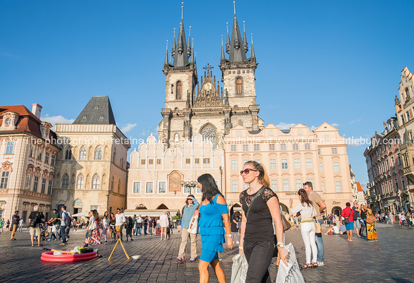 Sun highlights Gallery of Art over heads of crowd of tourists in front of gothic towers of Church of Our Lady before Tyn in Old Town Square in Prague, Czech Republic