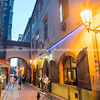 Restauranteur waits outside for patrons as people walk through narrow city lane