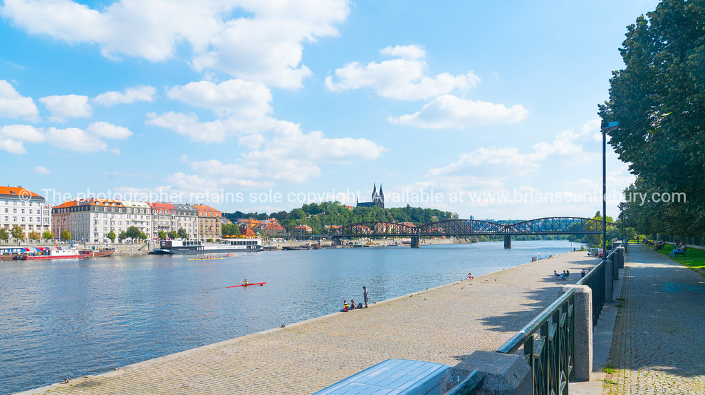 Characteristic architecture and tourist boats alongside promenade across river with arch bridge and Gothic church in distance and people rowing and enjoying the river.