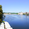 Small tourist boats on Vltava River surrounded by green river banks with renown bridges and classical Prague architecture under clear blue sky