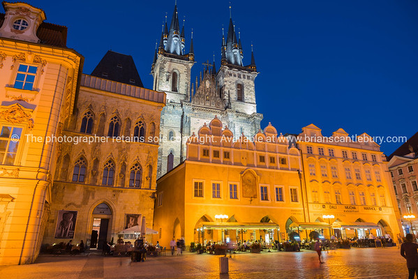 PRAGUE CZECH REPUBLIC - August 29, 2017;  Diner in glow illuminated buildings and gothic towers of Church of Our Lady of Tyn against dark sky.