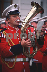 A band member plays the baritone while performing in front of the Prague Castle.