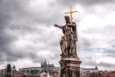 St John the Baptist with the Prague Castle in the background.  Prague, Czech Republic.