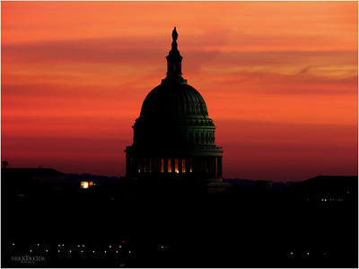 Capital building as the sun sets and casts an ominous orange glow.