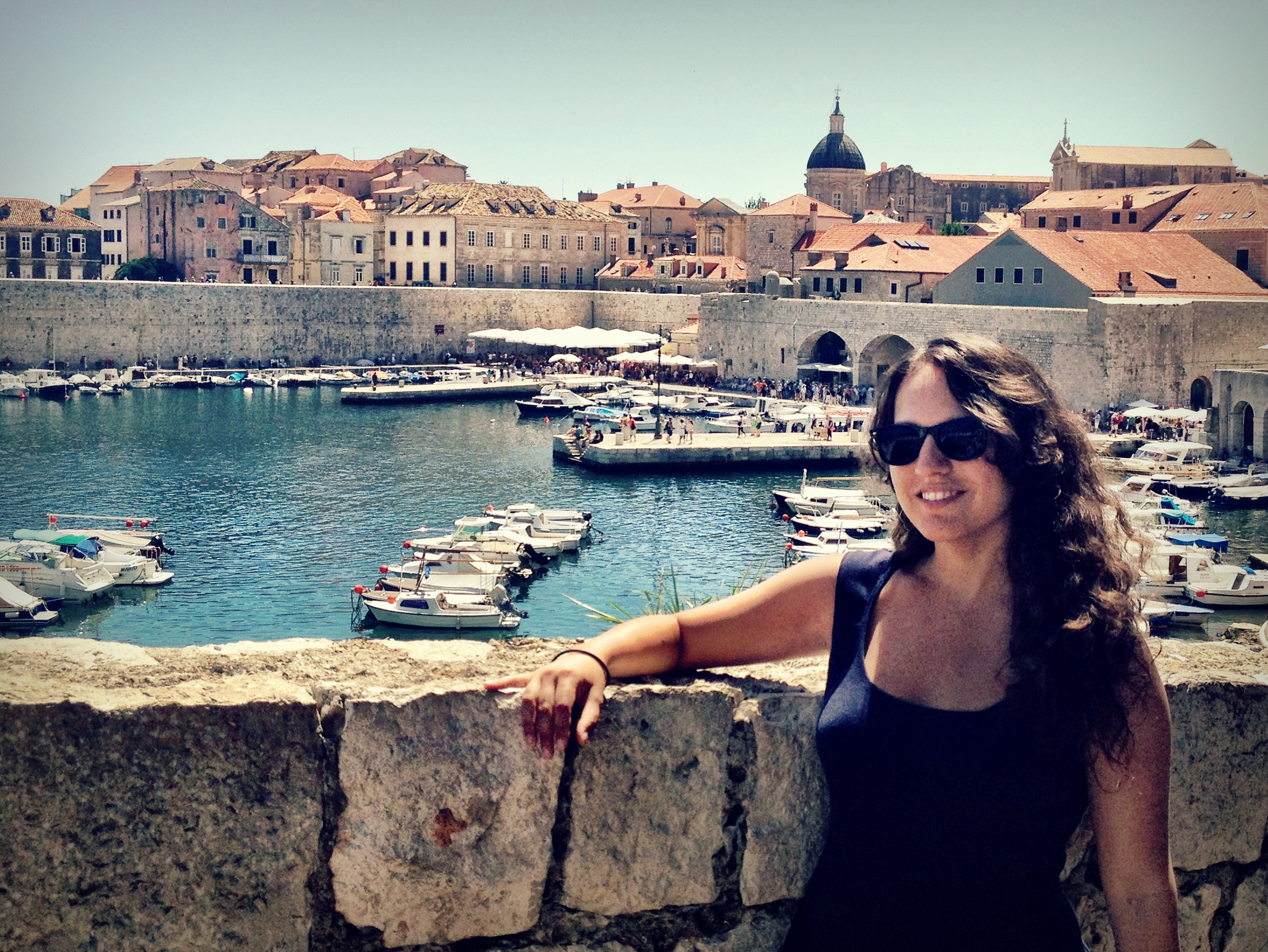 Kate wears a navy blue dress and sunglasses and poses in front of the old port of Dubrovnik, several boats in the water and the old city behind her.
