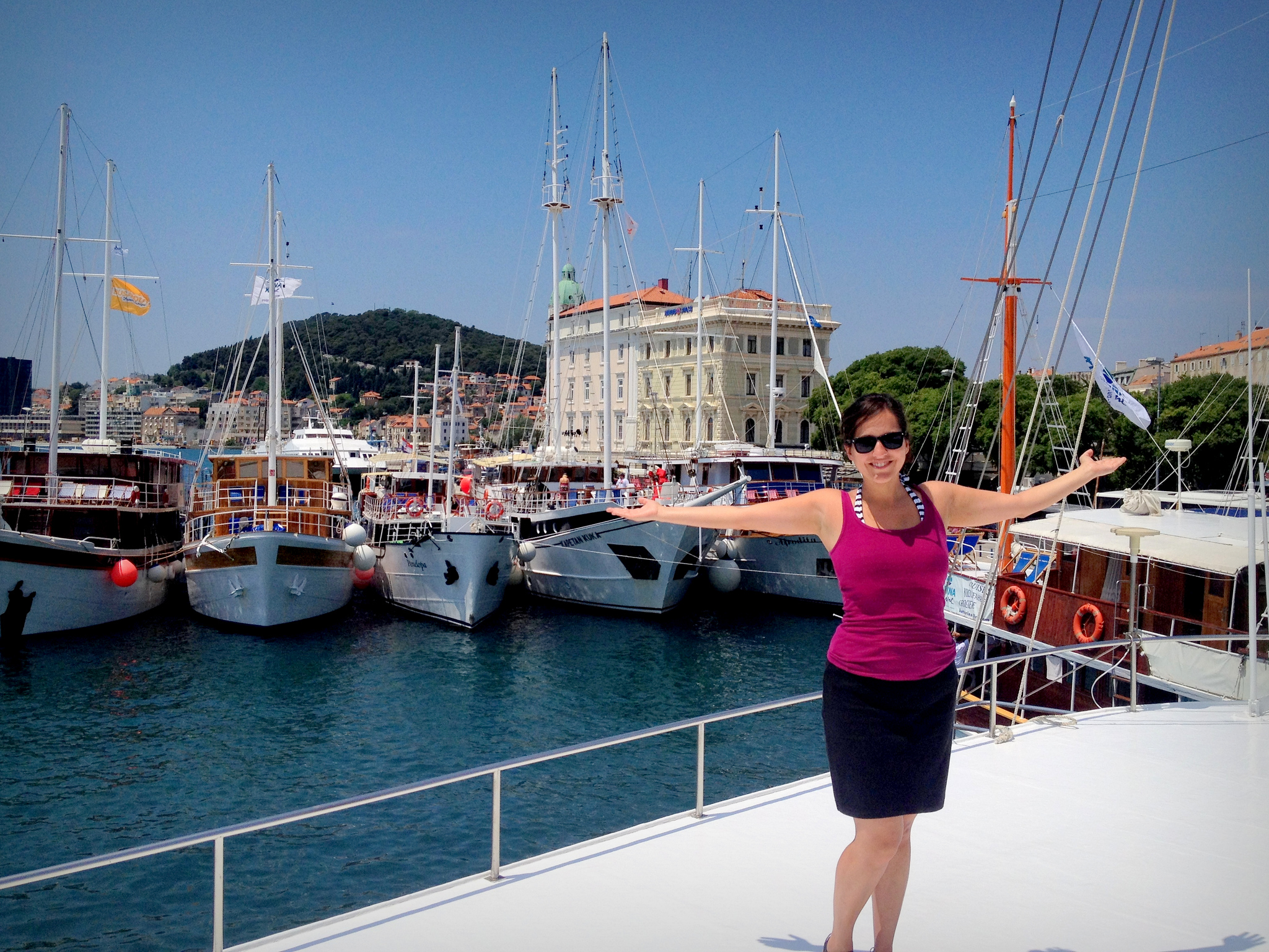 Kate wears a raspberry tank top and black skirt and poses with her arms out in front of the port of Split.