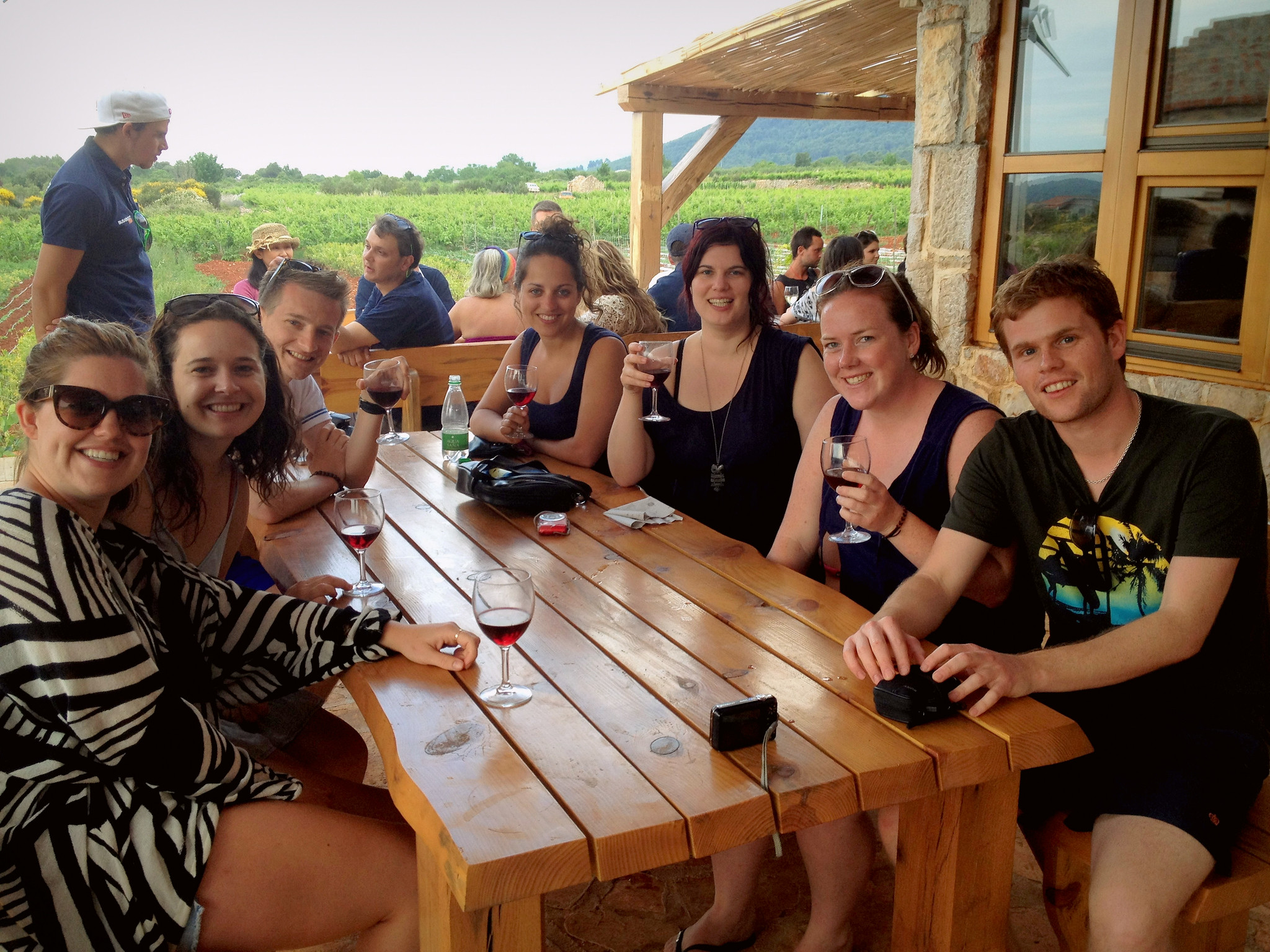 Kate and several friends surround a wooden picnic table in a vineyard, glasses of red wine in their hands.