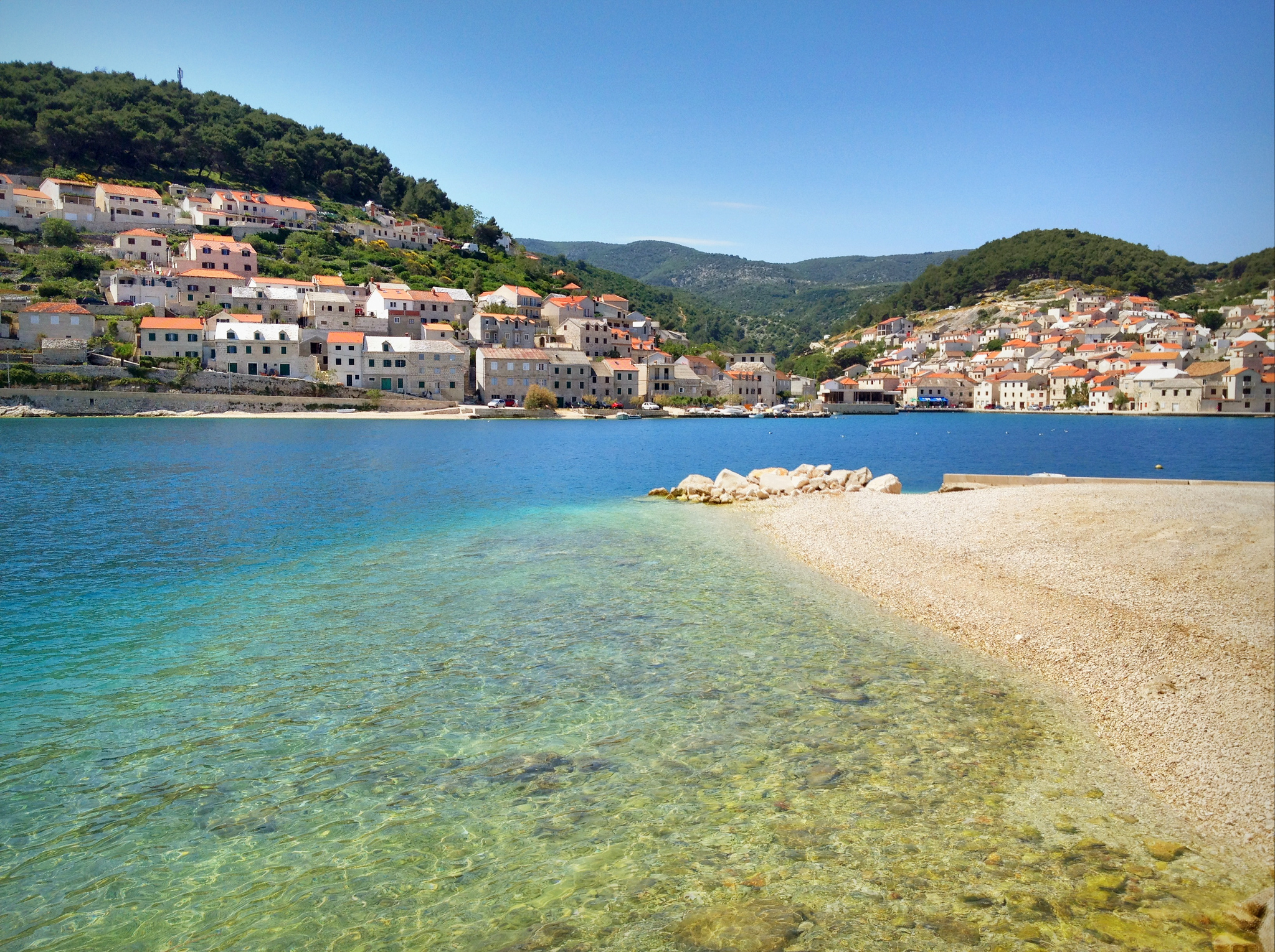 Pucisca, Croatia. A white stone beach leads into clear turquoise water; in the background are white buildings with orange roofs in front of green hills.
