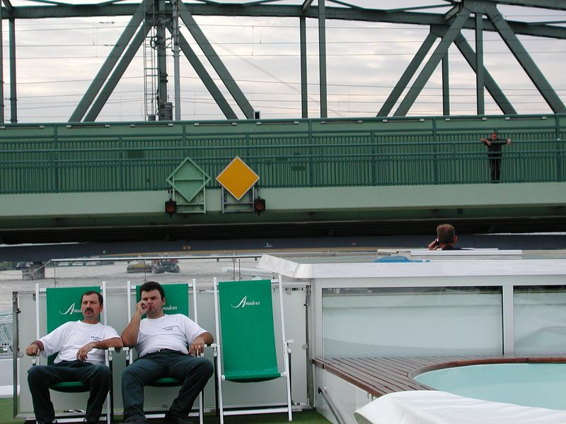 As the first low bridge approaches, the crew takes a rest, after collapsing canopies, hand rails, a wet bar, and more for this 30-minute trip upriver to our temporary dock for the night.