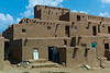 """Taos Pubelo is the oldest continuously occupied structures in the Americas. The """"Red Willow"""" tribe have used this building for 1,300 years. Built of adobe, the building is 5 stories tall and until the 20th century had no doors in the wall. Entry was gained via ladders to roof top opening. In the event of an attack by neighboring tribes, the women and children entered the building and pulled the ladders up where three foot thick adobe walls offered fortress like protection."""