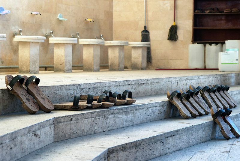 Bathing station inside a Mosque with shoes ready.