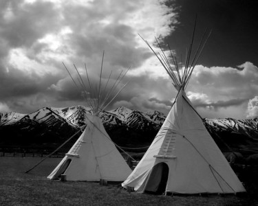 "Two lodges. While most folks call these ""tipis"" or ""teepees,"" people who own and use them, including native Americans, call them ""lodges."" This also gives us the name of the tree from which the poles are taken: the lodgepole pine. The Wellsville Mountains can be seen in the background."
