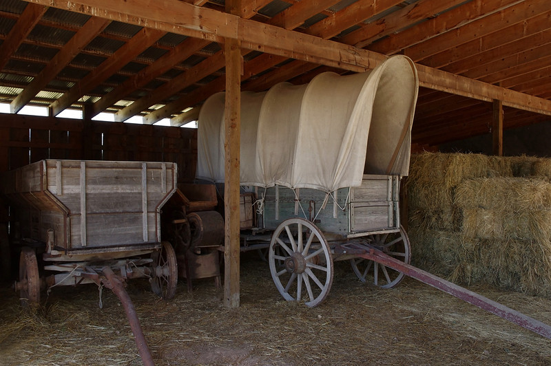 Covered wagon and hay in the pole barn, Bakersville - a seed store and fantasy town near Mansfield, Missouri.