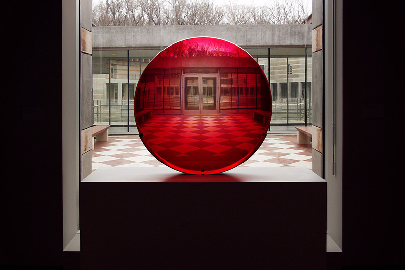 Red glass disc - an untitled work by by artist Fred Eversley. Crystal Bridges Museum, Bentonville, Arkansas.