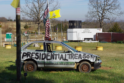 """Stopped briefly to photograph a roadside attraction - a bizarre political statement, in mixed media.   By mixed media, I mean old cars spray painted with slogans, flags, a portable sign, mannequins and army surplus guns.  """"Peter's Moonlight Naughty Resort""""?"""