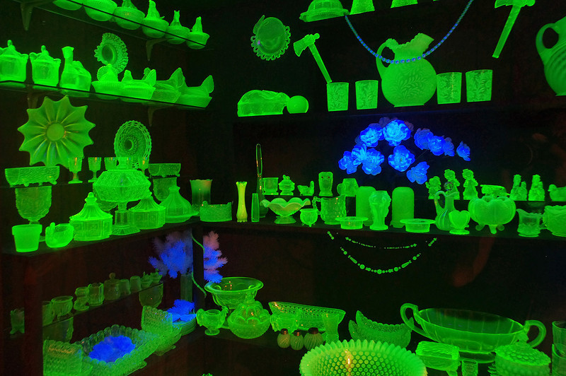 "Display of Fenton ""Vaseline"" glass items under ultraviolet light.Golden Pioneer Museum on Highway 86 in Golden, Missouri; radium added to the glass produces the effect seen here."