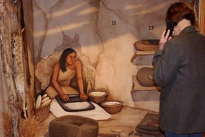 Rita listening to the audio intrepretation while viewing a stone metate, Museum of Native American History, Bentonville, Akansas.