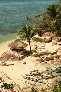 De lokalen verzamelen zich 'in de schaduw' in het haventje van Coco White Beach. Anda, Bohol, de Filipijnen.