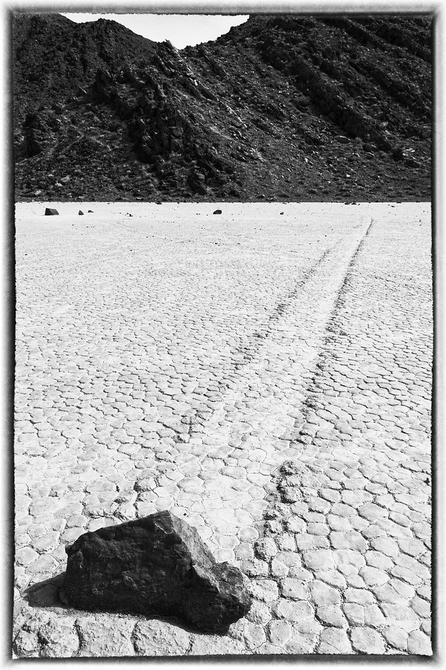"""Some of the rock paths are straight as an arrow. All of the rocks originate from the steep slope in the background of volcanic rock, a """"birthing"""" slope. From there they migrate all over the playa."""