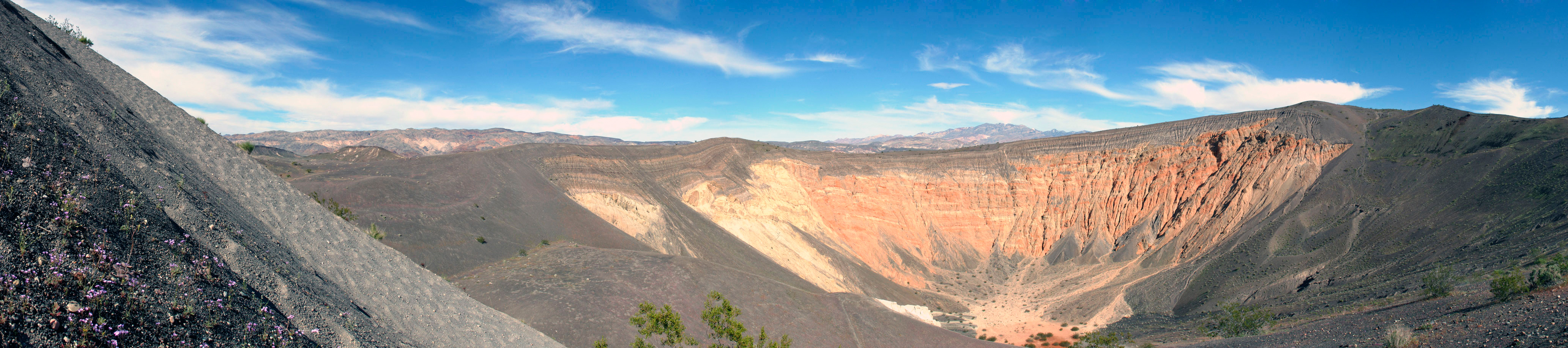"This is Ubehebe Crater, proof that Death Valley did indeed have volcanic activity at one time and is not just a big stretch mark on the Earth. <p> This is a ""created"" photo, in that it's a carefully taken and assembled series of photos.  In this case, 15 photos are stitched into this one result.  I had to stand here quite a bit to get this without any people in it.  Remember, we're in a National Park now, that's experiencing what is perhaps a once in a lifetime event.  There are LOTS of people here with us including the requisite tour bus of foreign language speakers and tons of irreverent teenagers.  But, you don't see any of them in this photo, do you? </font>"