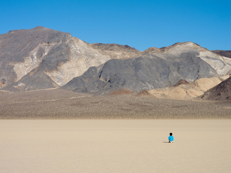 """<span id=""""title"""">Blue Shirt</span> <em>Racetrack Playa</em> This kid was part of a large family that was pretty spread out between the parking area and the Grandstand. His shirt matches the sky so nicely. I wanted to get a photo of him standing, but I guess it was time to sit down."""