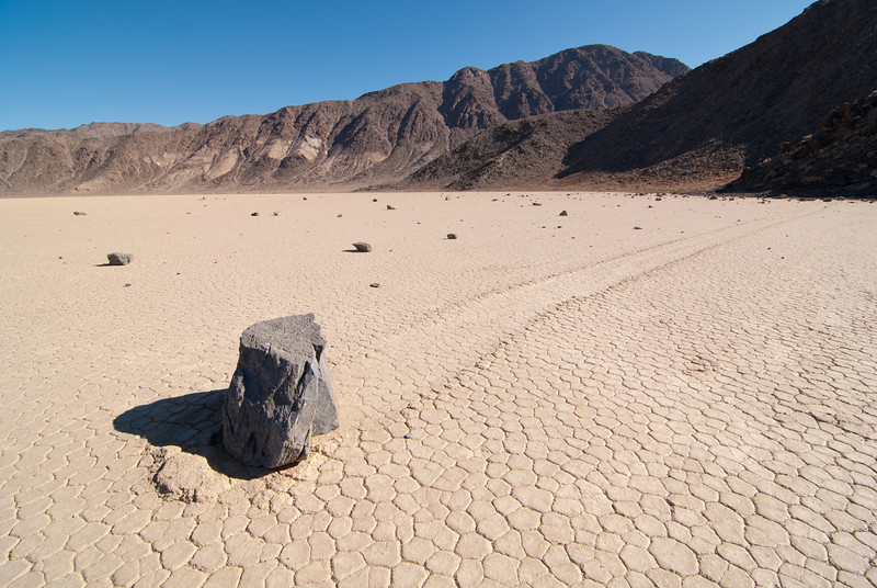"""<span id=""""title"""">Rock Trail 3</span> <em>Racetrack Playa</em> Here you can see how many other rocks are in the area - it's quite a few. The subject of this photo was particularly interesting because it had so much mud pushed out in front of it."""