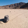 "<span id=""title"">Rock Trail 3</span> <em>Racetrack Playa</em> Here you can see how many other rocks are in the area - it's quite a few. The subject of this photo was particularly interesting because it had so much mud pushed out in front of it."