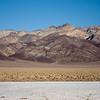 """<span id=""""title"""">Bands</span> <em>West Side Road</em> Here you can see the salt flats right in front of the Devil's Golf Course, with colorful mountains in the background."""