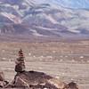 "<span id=""title"">Cairn</span> <em>Artists Drive</em> At the first pull-off along Artists Drive, we hiked up a small hill to see the view. At the top, there were several cairns - piles of rocks usually used to mark a trail. We saw them all over the place in Death Valley, but they were usually not needed. It seems like it's just a thing people do for the hell of it."