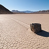 "<span id=""date"">_11/25/11_</span> <span id=""title"">Rock in Motion</span> <em>Death Valley, Day 3</em> If you've heard of it before, you probably recognize this as a photo of the Racetrack. If you haven't, let me tell ya: The Racetrack is a mud playa in Death Valley National Park, where the rocks move. No one has ever seen it happen and no one has been able to prove how it happens, but the evidence is right there - huge rocks with long mud trails behind them. The theory is that when the playa gets wet, it gets slippery enough that high winds are able to push the rocks around. It's a truly amazing place and I enjoyed every minute that we spent there. The road to it is not easy. You need an SUV at the very least - a lot of people rent Jeeps to make the trip. It's a long trip, too - took us most of the day, and we left pretty darn early.  Here's what the National Park Service Sign says: <em>""The moving rocks are something of a mystery. Scientists theorize that when this ancient lake bed - or playa - gets wet, it becomes so slippery that winds can move rocks weighing 100 pounds or more. Others suggest that winds move the rocks only when ice helps them raft along a temporary lake surface."" </em> <a href=""http://www.jawsnap.net/Travel/DeathValley2011/20327429_xbqMPq"">More Death Valley Photos</a>  <a href=""http://www.jawsnap.net/Daily/year3/11272102_ACXDJ#1104920556_ezUMh"">[last year]</a> <em>huh, a year ago we walked across lava flats...<em>"