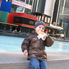 Michael, in NYC, eating a stand-bought hotdog, at Rockefeller Center, with a Christmas choo choo in the background.  DONE.