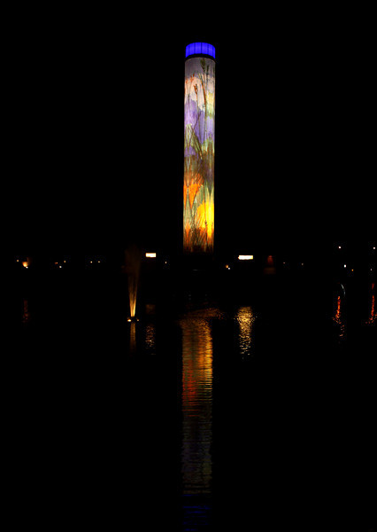 "At night the Paragon Prairie Tower is carefully illuminated so there are no ""hot spots"" but evenly lit.  The top is internally illuminated.  To the right is the small fountain and its reflection."