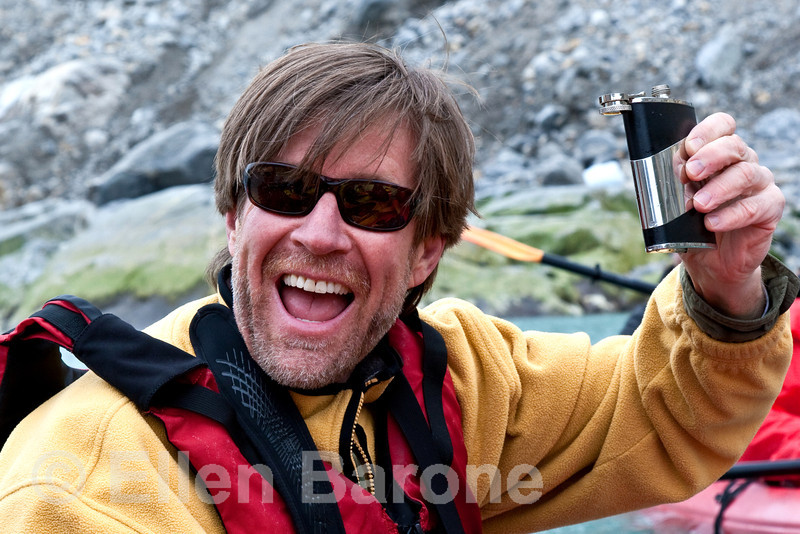 A happy sea kayaker enjoys a nip. Sea kayaking, Inside Passage, southeast Alaska, USA.