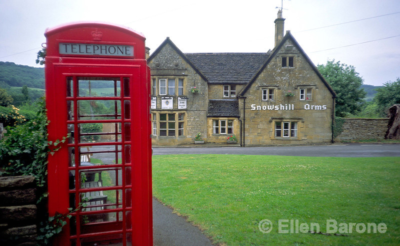 The sleepy Cotswold village of Snowshill looks like a movie set with its distinctly British icons, a red phone box, village green, and local pub. Snowshill, the Cotswolds, England.